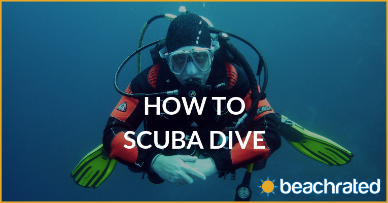 man wearing red scuba diving with nothing around him and folding his hands in front and staring into the camera