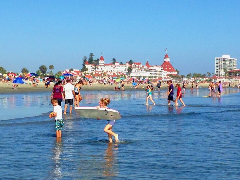 kids and families at coronado beach with red roof building in the background