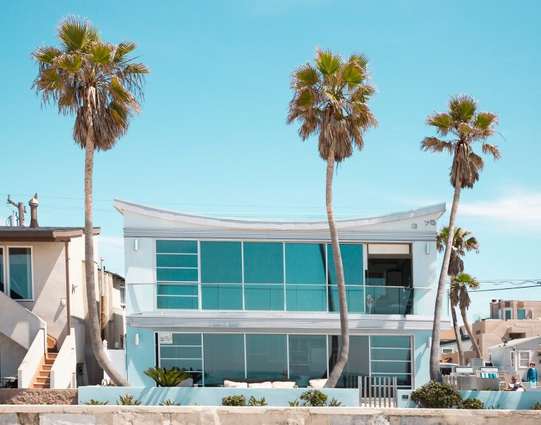 bright beach house with lots of windows and 2 palm trees at salt creek beach california
